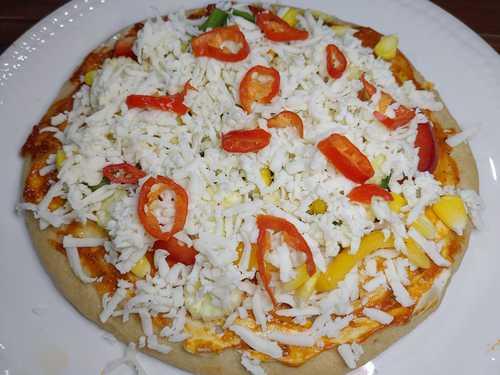 adding cheese to veg pizza recipe